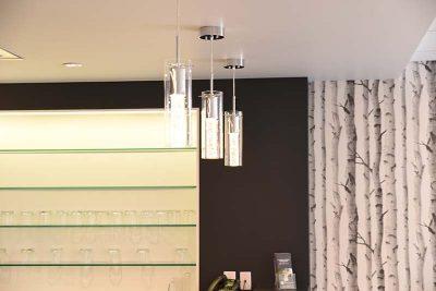 Les stylistes de chez Signé Labelle ont conçu cette éclairage et la disposition de l'étagère derrière le bar