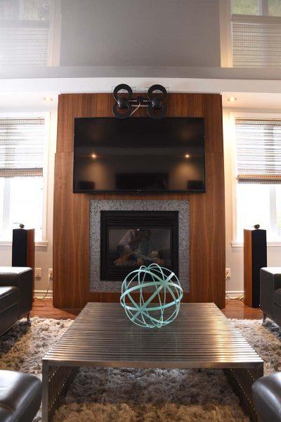 Aménagement d'un manteau de foyer en bois naturel et d'un salon conçu par Signé Labelle